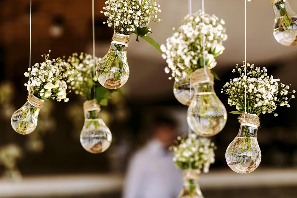 How Much Does a Professional Wedding Decorator Cost?  https://www.shutterstock.com/image-photo/original-wedding-floral-decoration-form-minivases-354527417   Some people have a gift for creating an elegant ambiance, and others, like myself simply do not.   And while your main memory of your wedding will be about your exchange of heart-felt vows, what your guests will remember is all the nice details. You should give them something to remember your wedding day as long as you will.   But, do you really want to hire a wedding decorator? On the one hand you can be assured of a stunning venue, but on the other hand, you have to consider the cost.  There are several expenses that go into making the perfect wedding, and do you really want to add to it by hiring a wedding decorator if you can get away with not doing it?  To help you answer these questions, in this article, we're going to look at what a wedding decorator is and what they actually do. Then we're going to dive into the pros and cons of hiring a wedding, before covering the average cost of hiring a wedding decorator.  At the end of the article, we'll sign off with a brief conclusion. (Please feel free to scroll ahead to any section that interests you.) What Is A Wedding Decorator? What Do They Do? https://www.shutterstock.com/image-photo/happy-young-businesswoman-wearing-earphones-enjoying-1801130773   As the name suggests, it is the job of a wedding decorator to decorate your wedding venues, from the wedding ceremony itself through to the meal and the evening bash.  What does a wedding decorator do?  But as to what exactly that entails depends on the wedding decorator you have chosen…  Some wedding directors will expect you to have some general ideas about what you want in terms of color schemes or themes. They may even expect you to pay for all the decorations yourself in addition to their fee.  Other wedding decorators on the other hand will suggest various ideas to you, and include the price of the wedding d